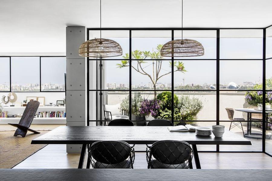 דירה בתל אביב חלון בלגי ברזל עם חלוקות בעיצוב קלאסי ופרופיל ברזל מינימליסטי בצבע שחור עם זכוכית בידודית.